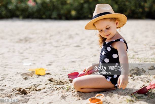 happy llittle girl having fun on sand - uv protection stock pictures, royalty-free photos & images