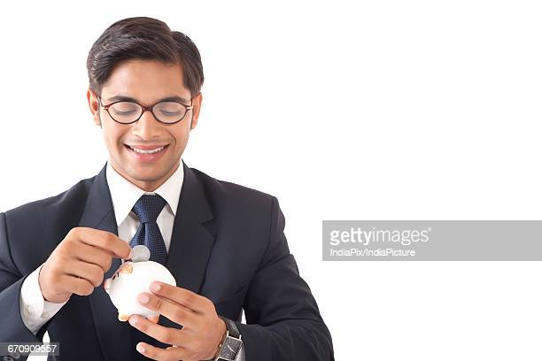 Happy looking young professional man dropping coin in small piggy bank against white background