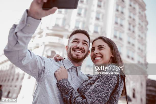happy loving couple taking selfie on city street - aleksandar georgiev stock photos and pictures