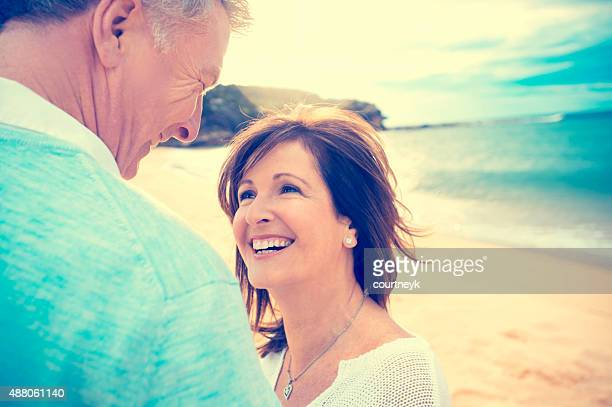 Happy loving mature couple on the beach.
