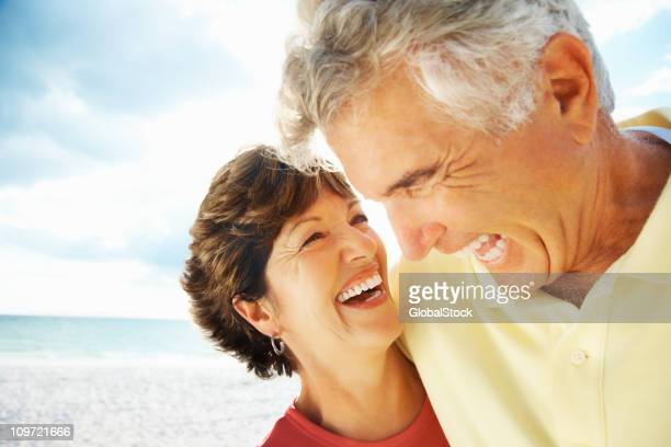 Happy loving mature man and woman laughing on beach