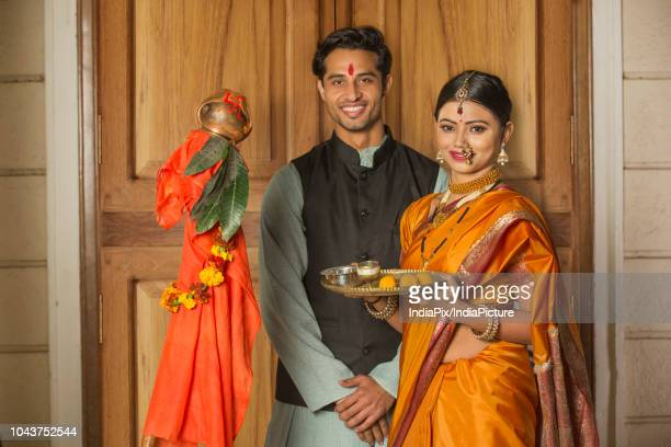 Happy maharashtrian couple in traditional dress celebrating gudi padwa festival holding a pooja plate and posing.