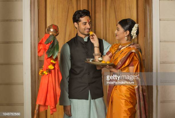 Happy maharashtrian woman in traditional dress offering sweet to her husband from pooja plate while celebrating gudi padwa festival.