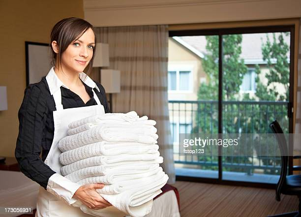 Happy maid, housekeeping with a stack of towels. Hotel room.