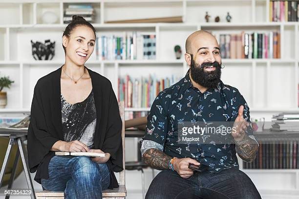 Happy male and female architects sitting at home office