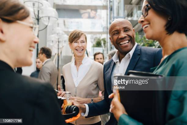 happy male and female business people talking while standing in office - employee engagement stock pictures, royalty-free photos & images