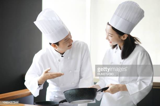 happy male and female chefs preparing food in kitchen - コック帽 ストックフォトと画像
