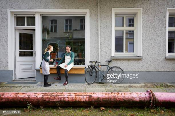 happy male and female colleagues outside art studio - doorway stock pictures, royalty-free photos & images