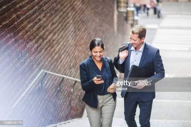 happy male and female entrepreneurs using phone while climbing staircase in city - vestuário de trabalho formal imagens e fotografias de stock