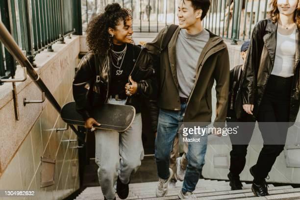happy male and female friends climbing steps at subway - verkehrswesen stock-fotos und bilder