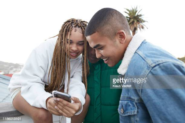 happy male and female friends looking at smart phone - facebook friends stock pictures, royalty-free photos & images