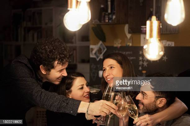 happy male and female friends raising toast during birthday celebration at home - four people foto e immagini stock