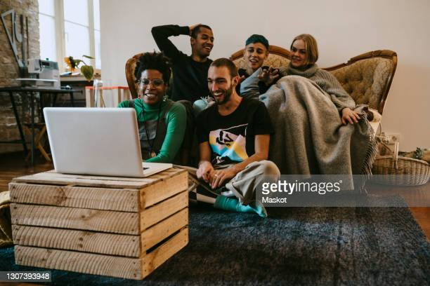 happy male and female roommates watching movie on laptop in living room - five people stock pictures, royalty-free photos & images