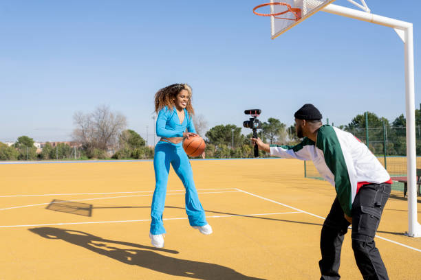 Happy male and female vlogging with basketball on sports court