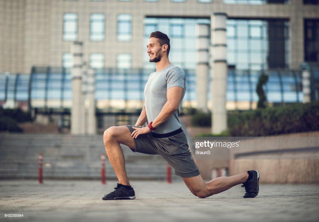 幸せなオスの運動選手が運動は、街に突進します。 : ストックフォト