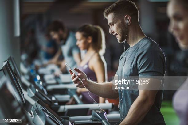 happy male athlete listening music on treadmill in a gym. - net sports equipment stock pictures, royalty-free photos & images
