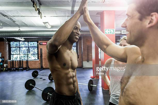 Happy male athletes giving high-five in gym