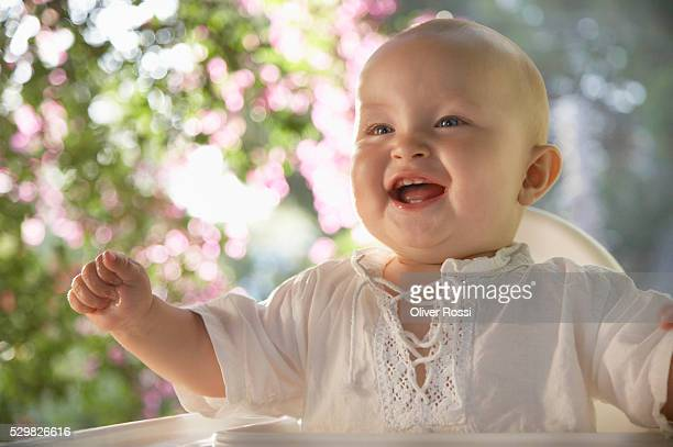 Happy male baby sitting in high chair