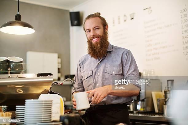 Happy male barista preparing coffee