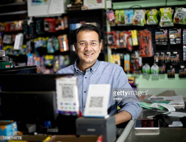 happy male cashier at supermarket - indian ethnicity stock pictures, royalty-free photos & images