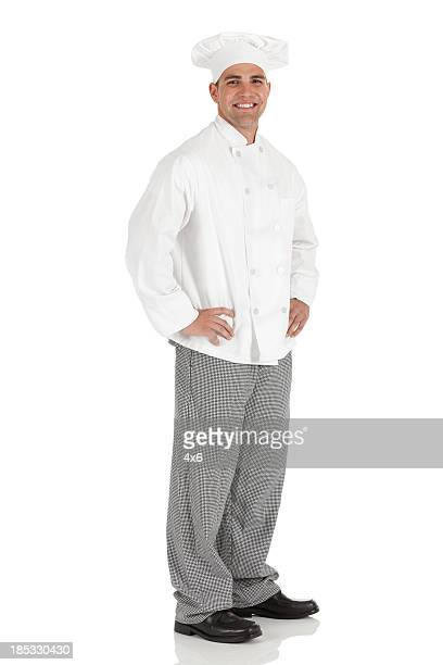Happy male chef standing with arms akimbo