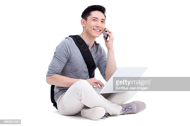 Happy male college student talking on the phone