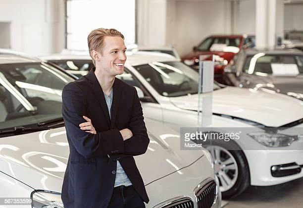 Happy male customer leaning on car at showroom