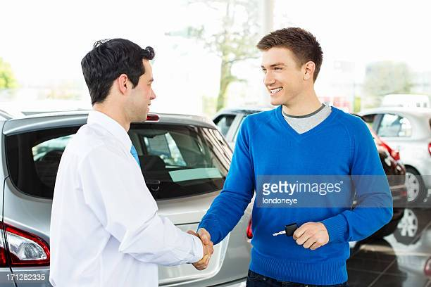 Happy Male Customer Shaking Hands With Salesperson