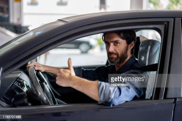 カメラで微笑むディーラーで車を試してみる幸せな男性の顧客 - 試運転 ストックフォトと画像
