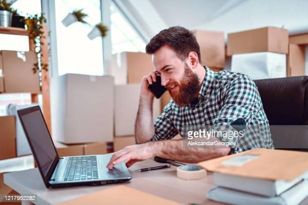 電話を使用している間にパッケージ追跡コードを入力する幸せな男性配達オフィスの労働者 - 追跡 ストックフォトと画像