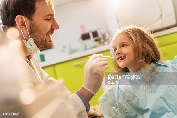 Glücklich Männlich Zahnarzt untersuchen kleine Mädchen putzen in Zahnarzt-Büro.