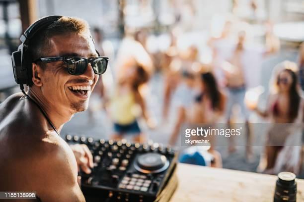 ビーチパーティーで音楽を再生幸せな男性の dj。 - クラブdj ストックフォトと画像