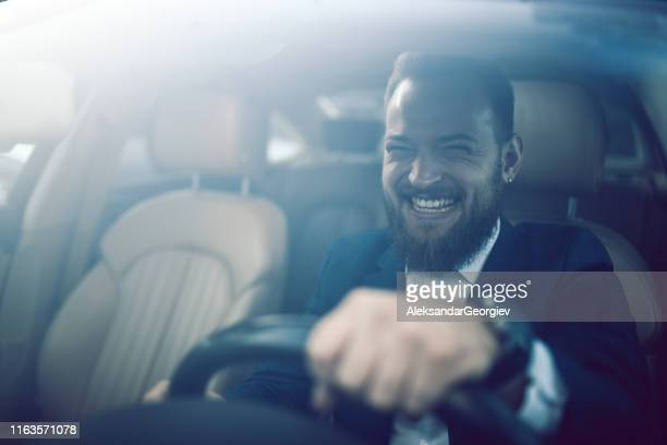 happy male enjoying driving luxurious car - domestic car stock pictures, royalty-free photos & images
