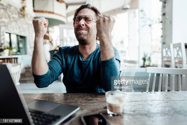 happy male entrepreneur doing fist by laptop in coffee shop - gewinnen stock-fotos und bilder