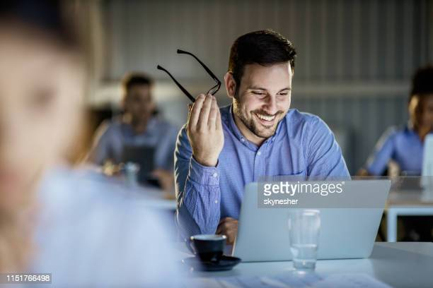 happy male entrepreneur reading an e-mail on a computer during education event in the office. - reading glasses stock pictures, royalty-free photos & images