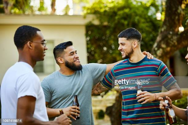 happy male friends enjoying beer at backyard party - men friends beer outside stock pictures, royalty-free photos & images