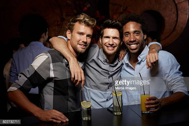 Happy male friends with drinks at nightclub