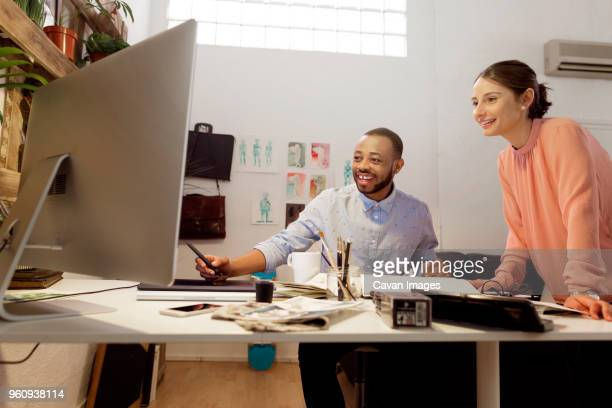 happy male illustrator discussing with colleague at desk in creative office - illustrator stock photos and pictures