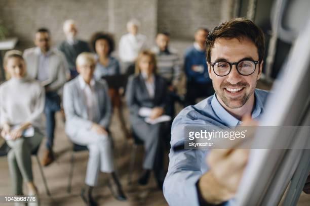 glücklich männlichen anführer verfassen eines businessplans auf whiteboard in einem konferenzraum. - seminar stock-fotos und bilder