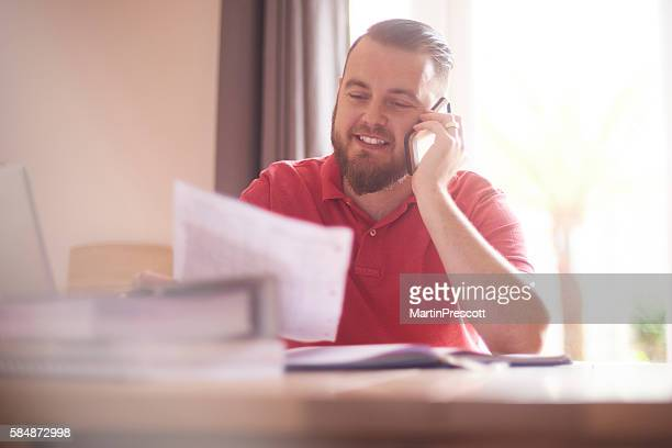 happy male on the phone with her mortgage company