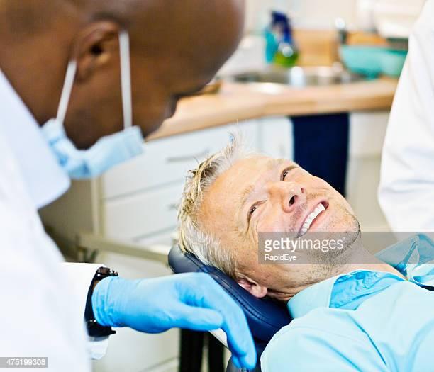 Heureux mâle patient en fauteuil dentaire dentiste souriant à son