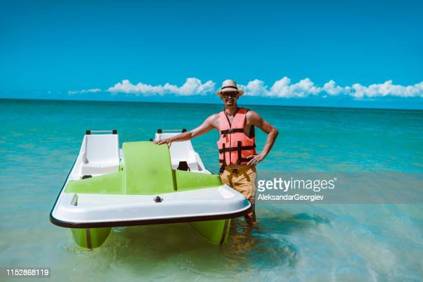 happy male presenting his favorite method of  beach fun - pedal boat stock pictures, royalty-free photos & images