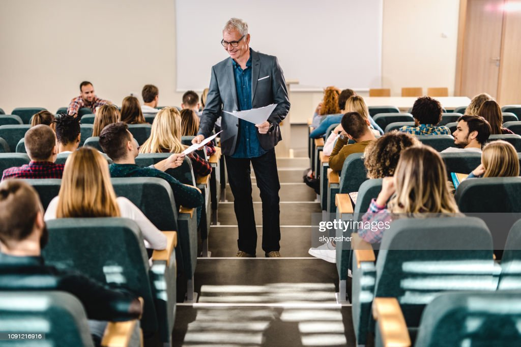 Happy male professor giving his students test results in amphitheater. : Stock Photo