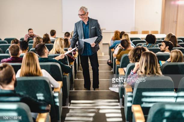 happy male professor giving his students test results in amphitheater. - professor stock pictures, royalty-free photos & images