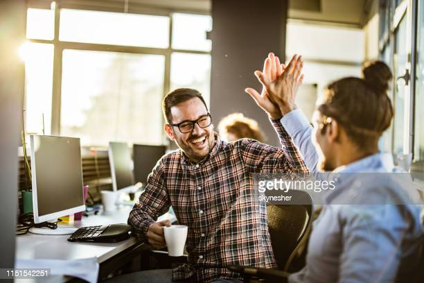happy male programmers giving each other high-five in the office. - congratulating stock pictures, royalty-free photos & images