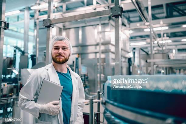 mâle heureux satisfait avec la quantité de production de jour - blouse de laborantin photos et images de collection