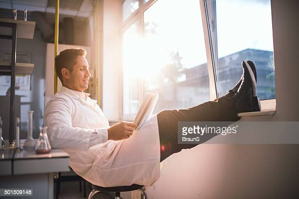 Happy male scientist reading scientific data in a laboratory.