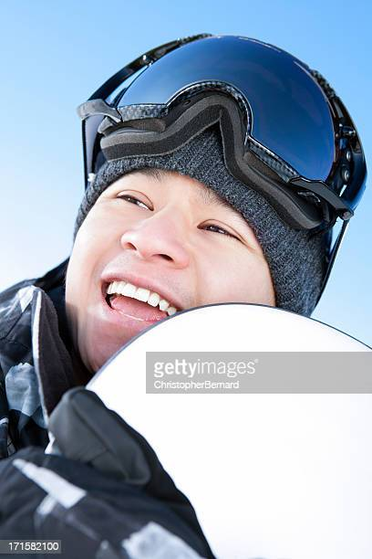 Happy male snowboarder against blue sky