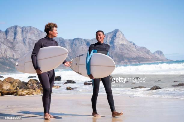os surfistas masculinos felizes estão andando na praia no verão - traje de mergulho - fotografias e filmes do acervo