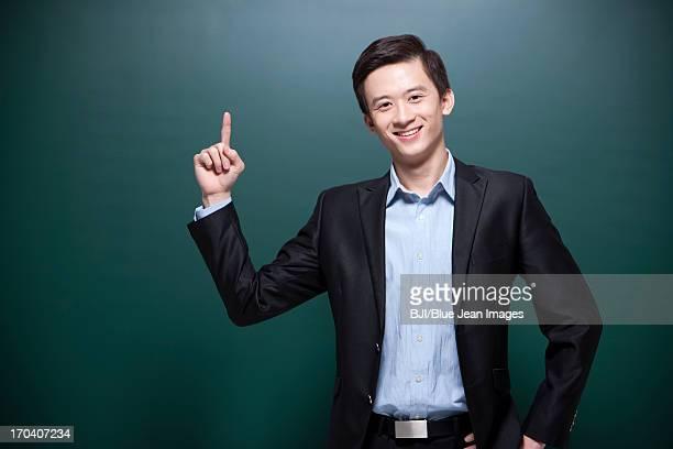 Happy male teacher raising finger up
